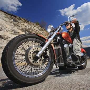 electroquest's motorcycle store, image of man riding a motorcycle with a rocky back-drop on a sunny day with white clouds, looking up from front wheel toward the back of the motorbike